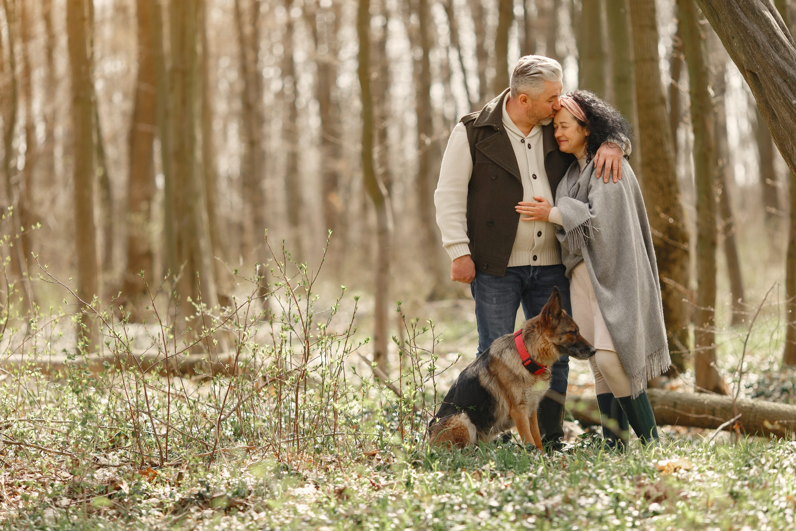 elderly-couple-walking-with-dog-in-fores